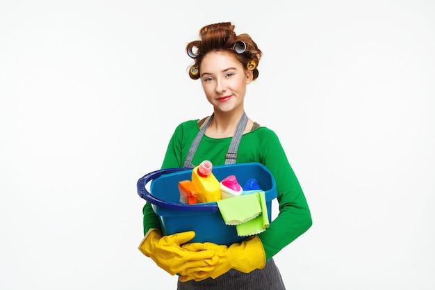 Adorável dona de casa posa segurando ferramentas de limpeza usando luvas amarelas Foto gratuita