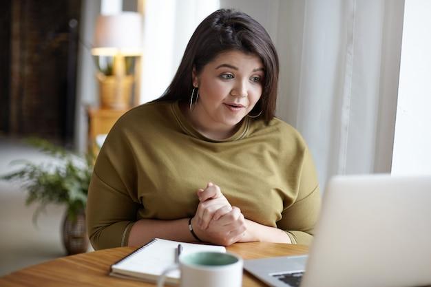 Adorável elegante jovem plus size mulher sentada em uma cafeteria aconchegante em frente ao laptop aberto, usando wi-fi grátis enquanto conversa online com sua amiga através de videochamada, com olhar animado. efeito filme Foto gratuita