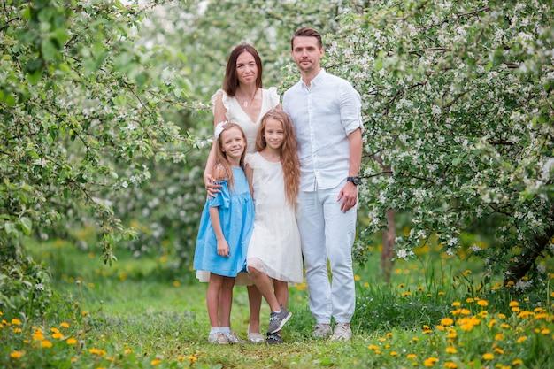 Adorável família no jardim desabrocham cereja em lindo dia de primavera Foto Premium