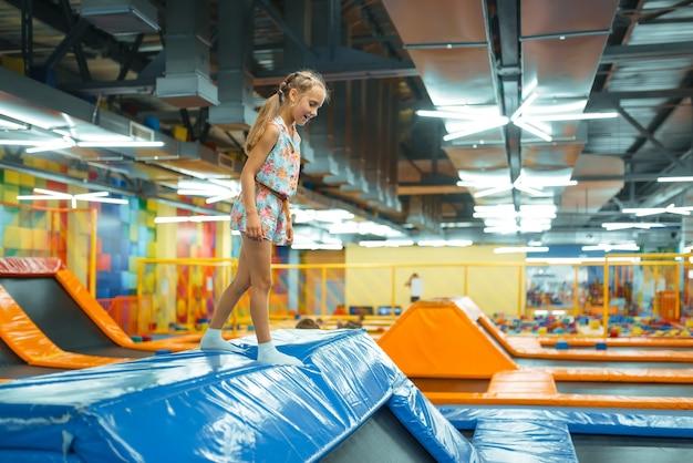 Adorável garota pulando na cama elástica de crianças, playground no centro de entretenimento. Foto Premium
