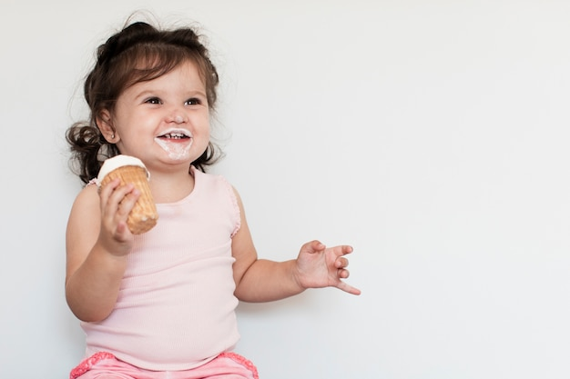 Adorável garota tomando sorvete e olhando para longe Foto gratuita