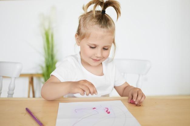 Adorável garotinha encantadora com rabo de cavalo sentada na mesa do jardim de infância em frente a um lençol branco, colorindo ou fazendo figuras usando plasticina ou argila, tendo uma expressão facial alegre e alegre Foto gratuita