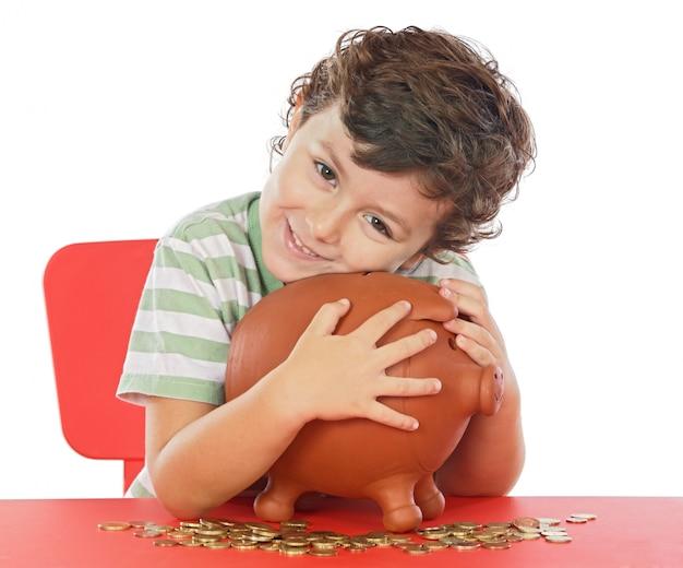 Adorável garoto colocando suas economias em sua caixa de dinheiro Foto Premium