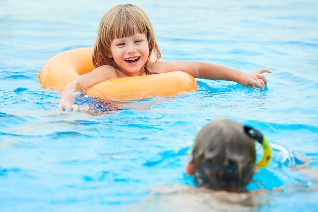 Adorável garoto nadando na piscina Foto gratuita