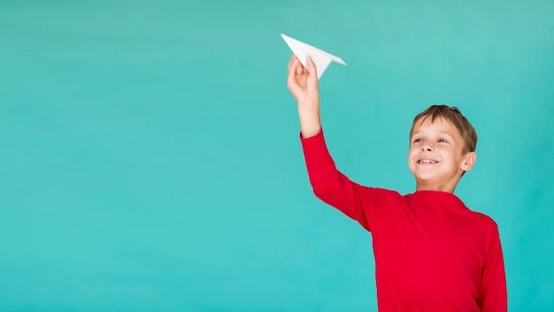 Adorável garoto segurando um avião de papel com espaço de cópia Foto gratuita
