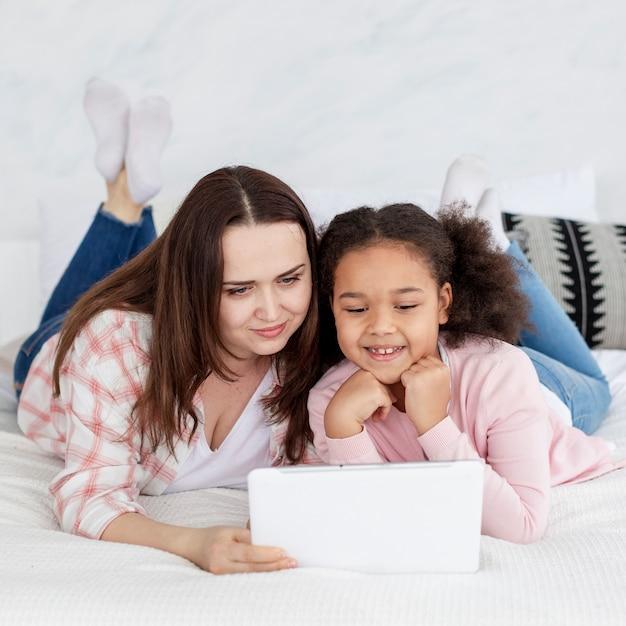Adorável jovem assistindo desenhos animados com a mãe Foto gratuita