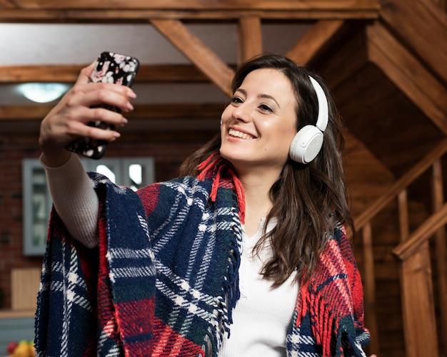 Adorável jovem com telefone e fones de ouvido Foto gratuita
