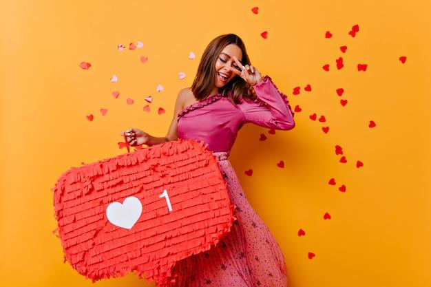 Adorável jovem de blusa rosa, dançando de felicidade. foto interna de uma blogueira deslumbrante sorrindo Foto gratuita