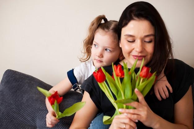 Adorável jovem mãe surpreendente com flores Foto gratuita