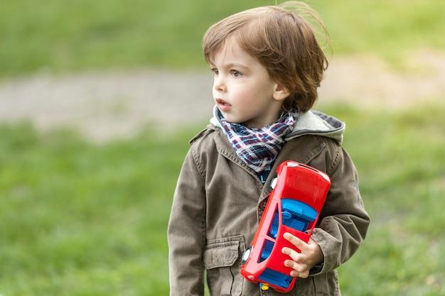 Adorável jovem rapaz com carro de brinquedo a desviar o olhar Foto gratuita