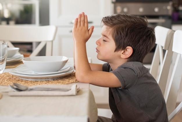 Adorável jovem rapaz rezando em casa Foto gratuita