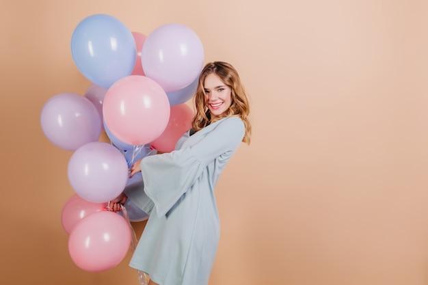 Adorável loira branca em traje azul posando com lindos balões Foto gratuita