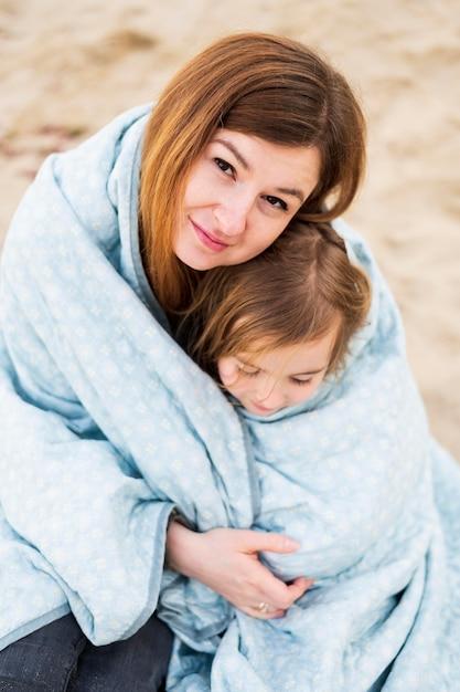 Adorável mãe e filha no cobertor Foto gratuita