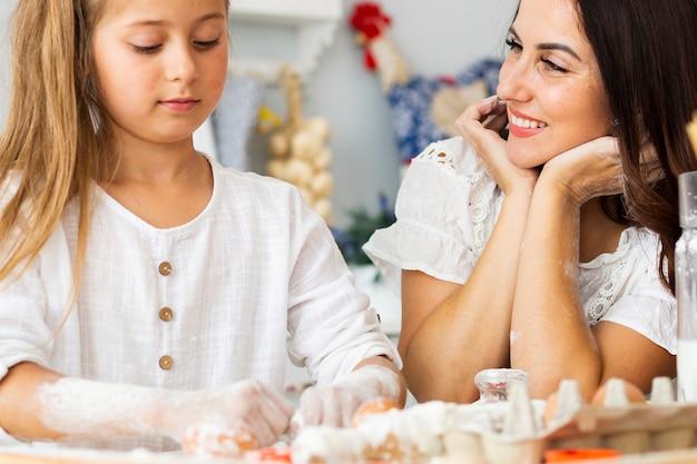 Adorável mãe e filha preparando comida Foto gratuita