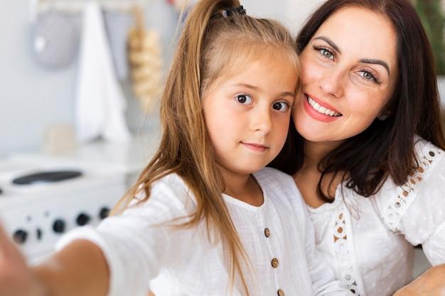 Adorável mãe e filha tomando selfies Foto gratuita