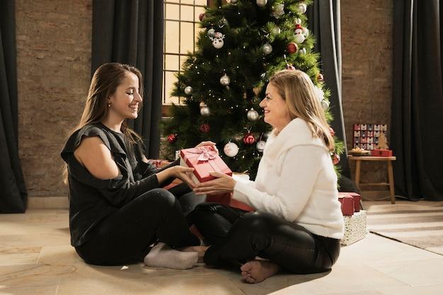 Adorável mãe e filha trocando presentes Foto gratuita