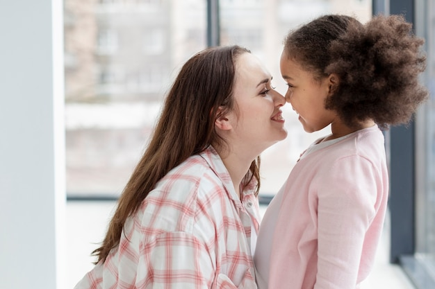 Adorável mãe feliz por estar em casa com a filha Foto gratuita