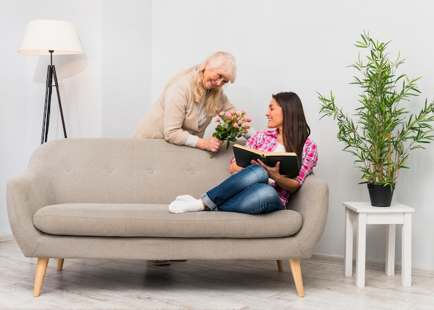 Adorável mãe senior sorridente dando buquê de flores para a filha sentada no sofá, segurando o livro na mão Foto gratuita