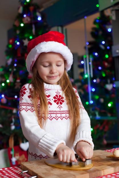 Adorável menina assar biscoitos de gengibre para o natal Foto Premium