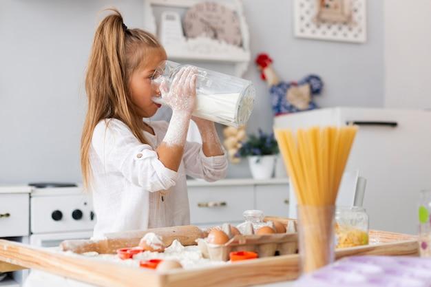 Adorável menina bebendo leite Foto gratuita