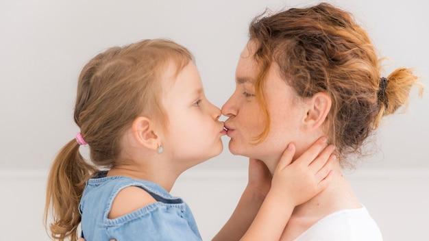 Adorável menina beijando sua mãe Foto gratuita