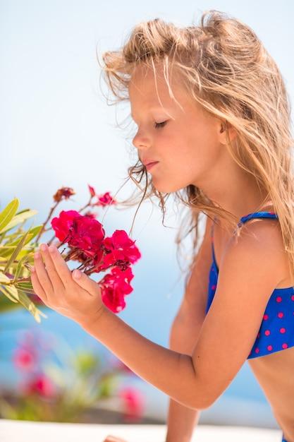 Adorável menina cheirando flores coloridas em dia de verão Foto Premium