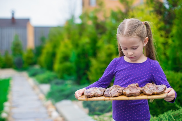 Adorável menina com bifes grelhados nas mãos ao ar livre Foto Premium