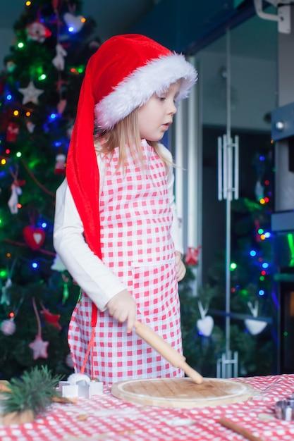 Adorável menina com chapéu de papai noel, assar biscoitos de natal de gengibre em casa Foto Premium
