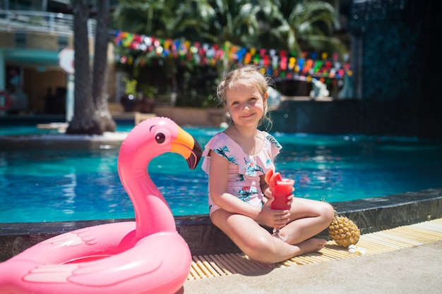 Adorável menina com flamingo rosa anel inflável bebendo suco de melancia Foto Premium