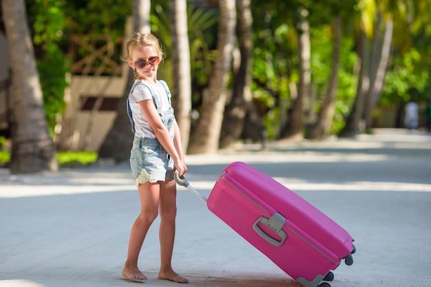 Adorável menina com grande bagagem durante as férias de verão Foto Premium