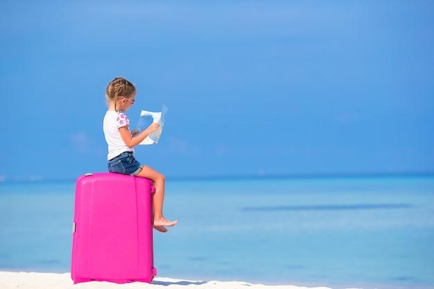 Adorável menina com grande bagagem e mapa da ilha na praia branca Foto Premium