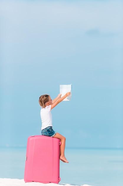 Adorável menina com saco grande na praia branca Foto Premium