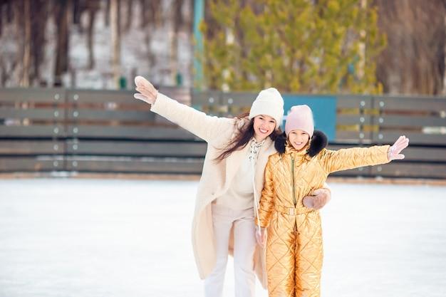 Adorável menina com sua mãe patinando na pista de gelo Foto Premium