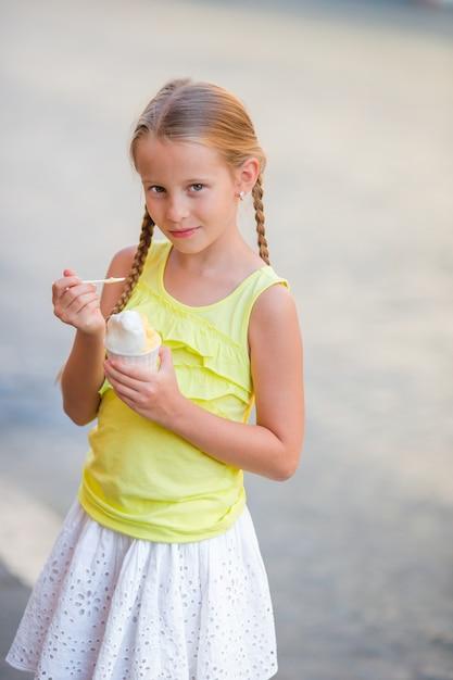 Adorável menina comendo sorvete ao ar livre no verão. garoto bonito, desfrutando de sorvete italiano real perto gelateria em roma Foto Premium