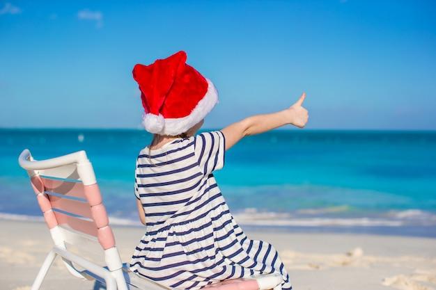 Adorável menina de chapéu de papai noel vermelho na cadeira de praia Foto Premium