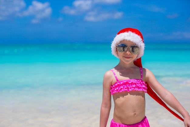Adorável menina de chapéu vermelho de papai noel na praia tropical Foto Premium