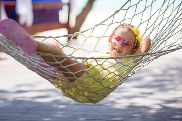 Adorável menina de férias tropicais relaxando na rede Foto Premium