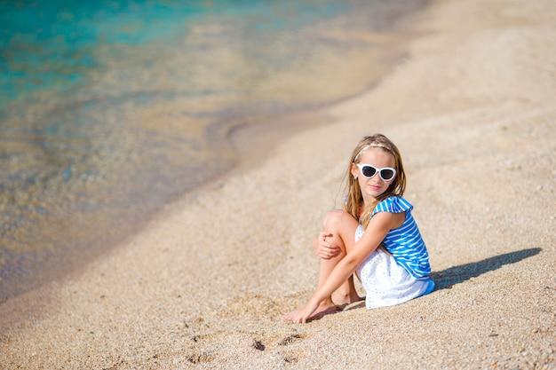 Adorável menina divirta-se na praia tropical durante as férias Foto Premium