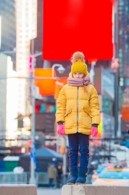Adorável menina divirta-se na times square, em nova york Foto Premium