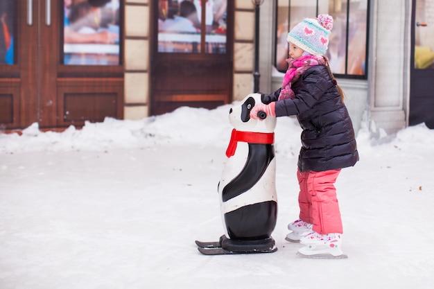 Adorável menina feliz desfrutando de patinar na pista de gelo Foto Premium