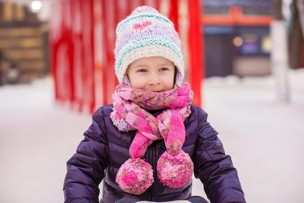 Adorável menina feliz patinando na pista de gelo Foto Premium