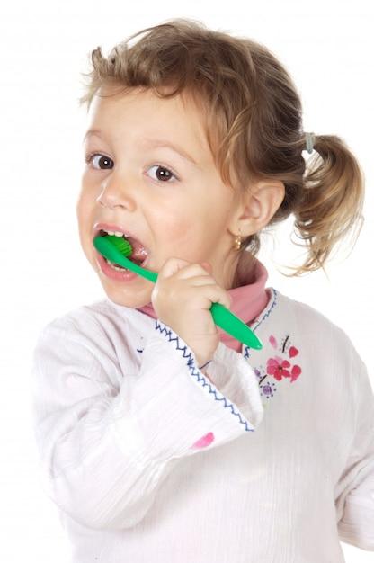 Adorável menina limpando os dentes um fundo branco Foto Premium