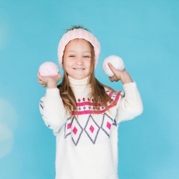 Adorável menina loira com bolas de neve Foto gratuita