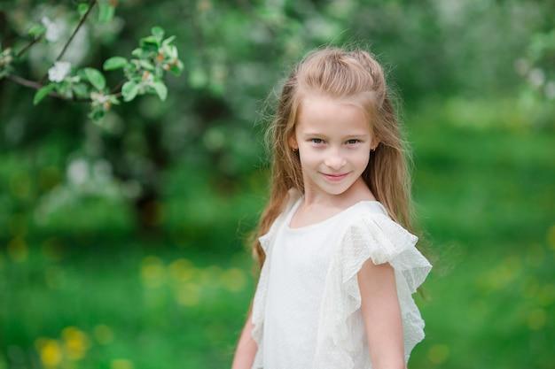 Adorável menina no jardim de apple florescendo em lindo dia de primavera Foto Premium