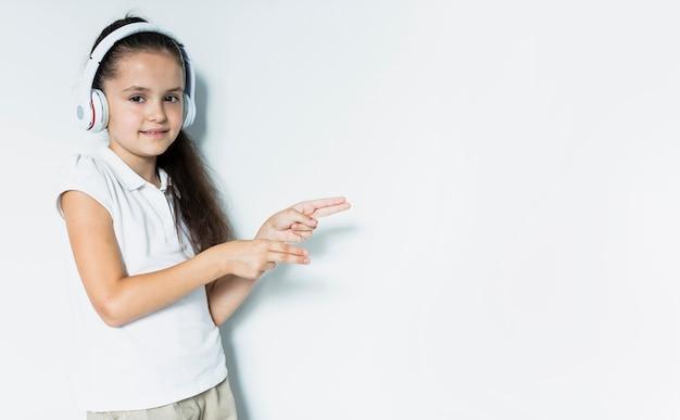 Adorável menina ouvindo música com fones de ouvido Foto gratuita