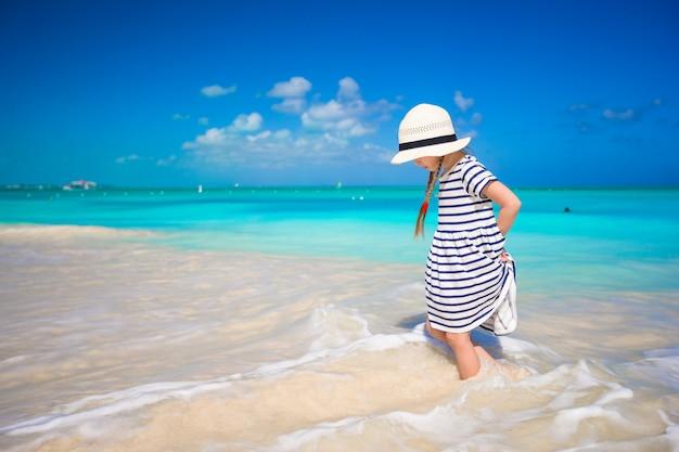 Adorável menina runing em águas rasas na praia exótica Foto Premium