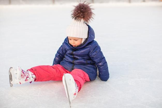 Adorável menina sentada no gelo com patins após a queda Foto Premium