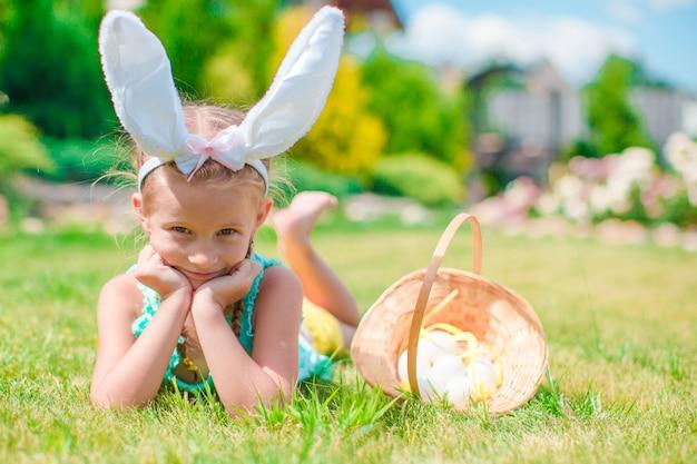 Adorável menina usando orelhas de coelho com ovos de páscoa no dia da primavera Foto Premium