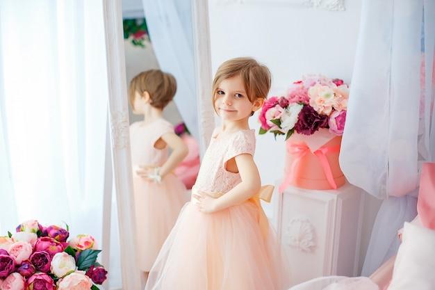 Adorável menina vestido posando e desviar o olhar na sala cheia de flores. Foto Premium