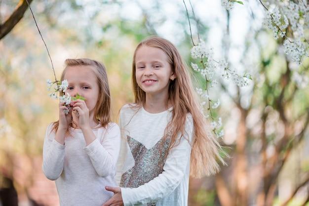 Adorável meninas no jardim de cerejeira desabrocham na primavera Foto Premium
